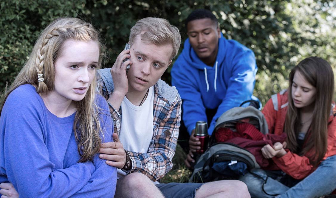A seated Allanah has wrapped her hands round her body as a friend makes a phone call. Two other friends are getting a flask from a rucksack.