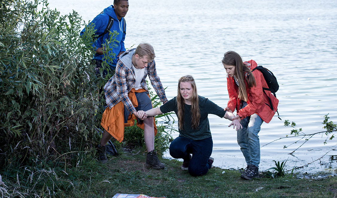 Allanah is kneeling and  facing away from the lake as two friends are supporting her arms and a third is watching.