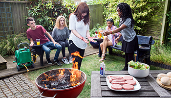 Flames are rising from a barbeque as a young person is looking at her outstretched hands with a pained expression. Four other look on.