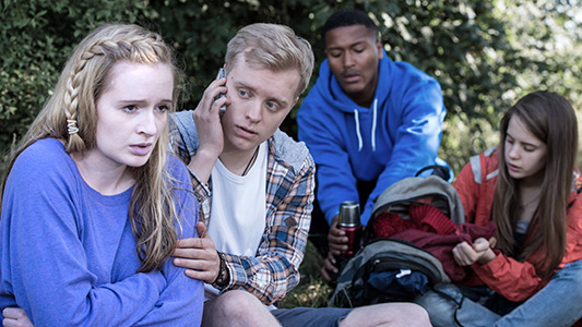A seated young person has wrapped her hands round her body as a helper makes a phone call. Two others are getting a flask from a rucksack..