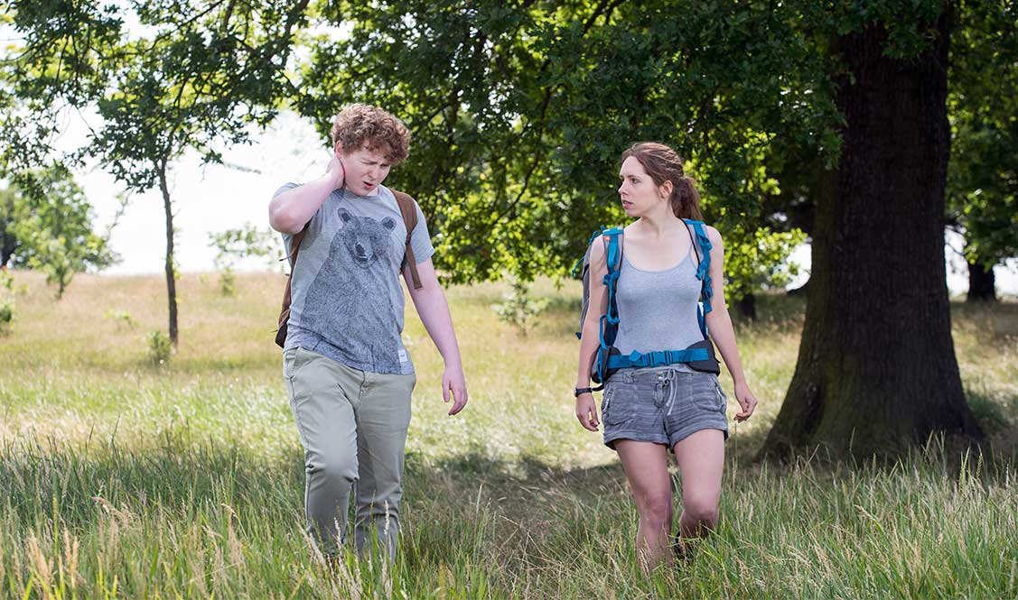 Finn is walking in a field. He has a pained expression and is holding his neck.  Joanna looks at him.