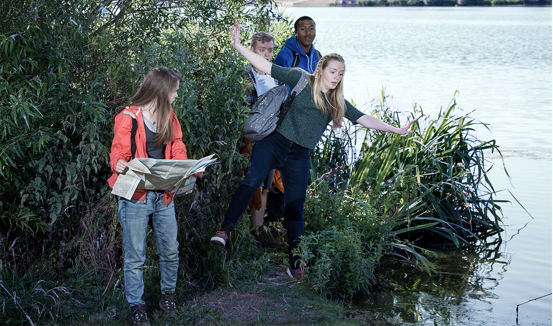 Allanah has outstretched arms and  is falling towards a lake as three of her friends look towards her.