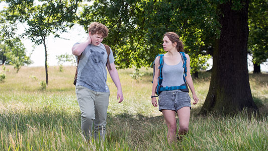 Young person is walking in a field. He has a pained expression and is holding his neck. A second person looks on.