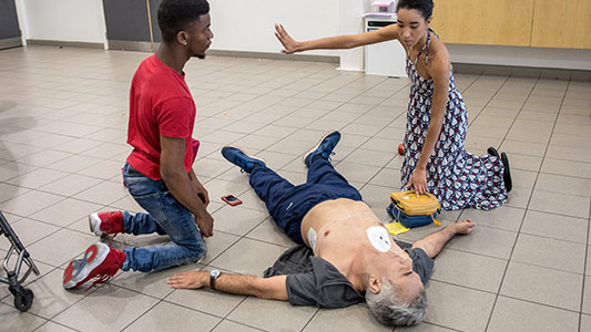 Two helpers are kneeling next to an unconscious man. One has a finger on an AED her other arm is outstretched with the palm raised.