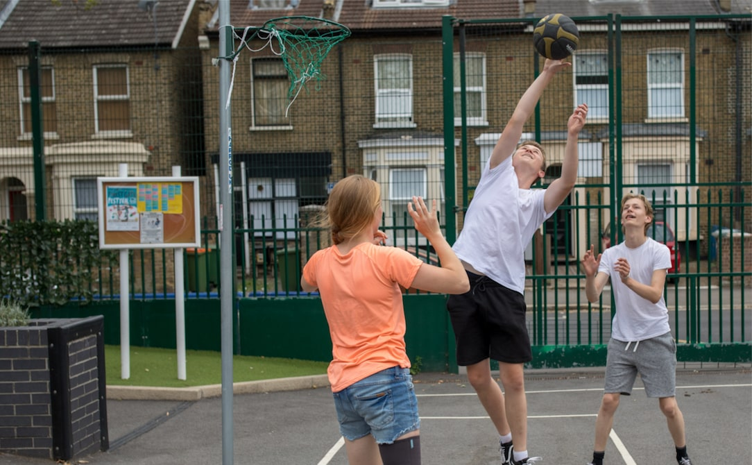 Three young people playing basketball.