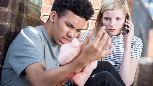Young person pressing a cloth onto his bleeding right forearm as someone watching him makes a phone call.